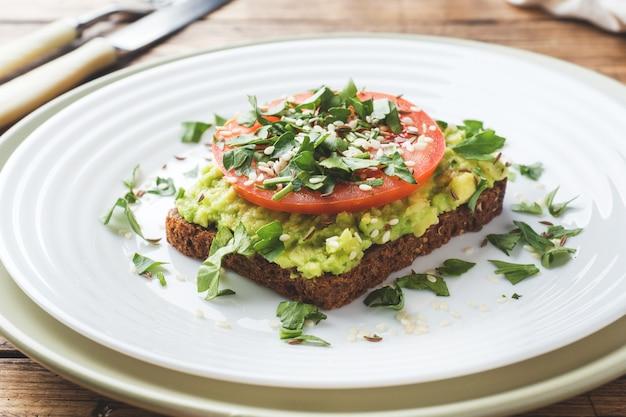 Avocado toast. gesunder toast mit avocadobrei und tomaten auf einer platte.