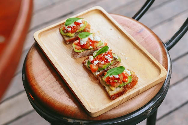 Avocado-toast mit cherry tomatoes und feta-käse, belegt mit rucola-blättern. auf holzstuhl serviert.