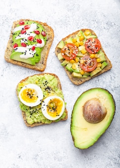 Avocado-toast mit ei, tomaten, gewürzen und einer hälfte der ganzen avocado über weißem steinhintergrund. gesunde frühstücks-avocado-sandwiches mit verschiedenen belägen, draufsicht, nahaufnahme