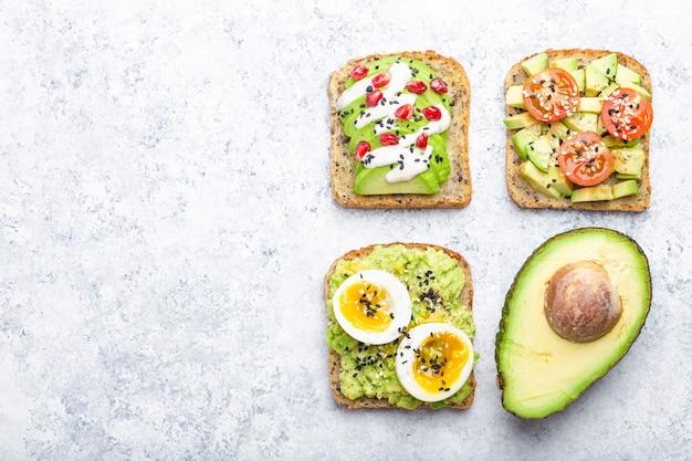 Avocado-toast mit ei, tomaten, gewürzen und einer hälfte der ganzen avocado über weißem steinhintergrund, platz für text. gesunde frühstücks-avocado-sandwiches mit verschiedenen belägen, draufsicht, nahaufnahme
