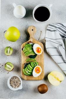 Avocado-toast mit eiern auf schneidebrett, früchten, samen, schwarzer kaffee. flachgelegt, draufsicht