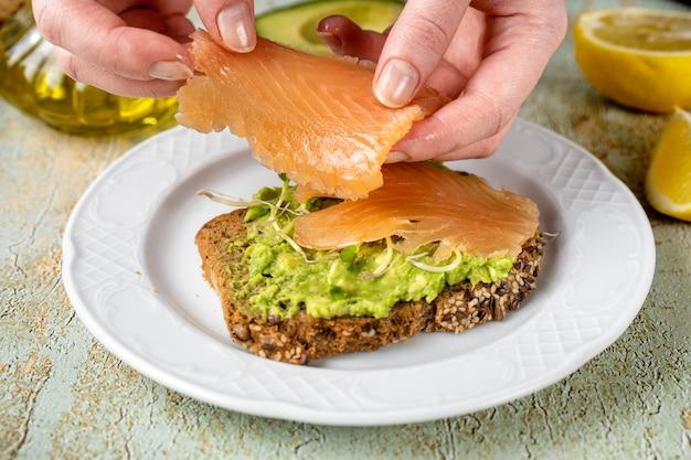 Avocado-toast mit gesalzener lachsscheibe von frauenhänden auflegen