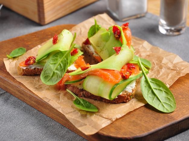 Avocado-toast mit gurkenfrischkäse und sonnengetrockneten tomaten
