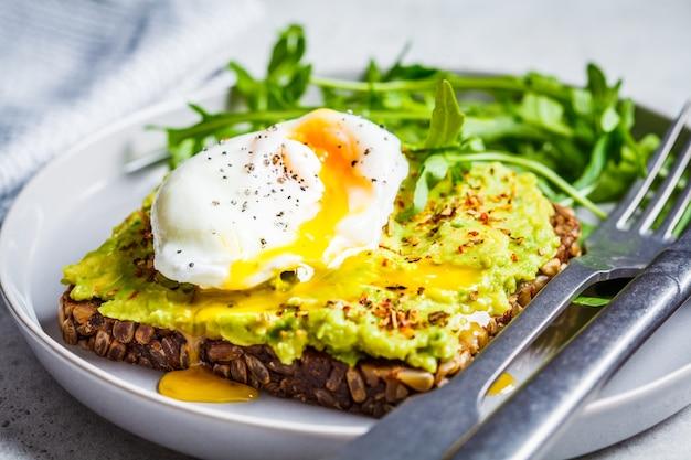 Avocado-toast mit pochiertem ei auf einem grauen teller. vegetarisches gesundes lebensmittelkonzept.