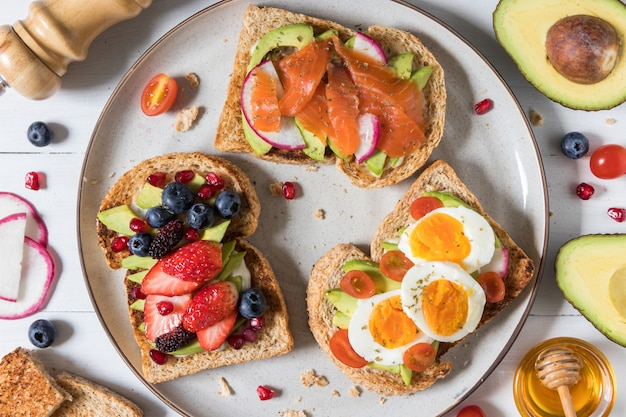 Avocado-toast mit verschiedenen belägen, darunter lachsfisch, eier, beeren