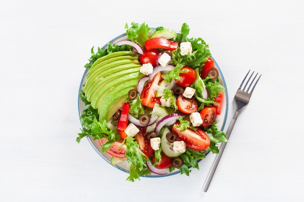 Avocado-tomatensalat nach griechischer art mit feta-käse, oliven, gurke, zwiebel, salat