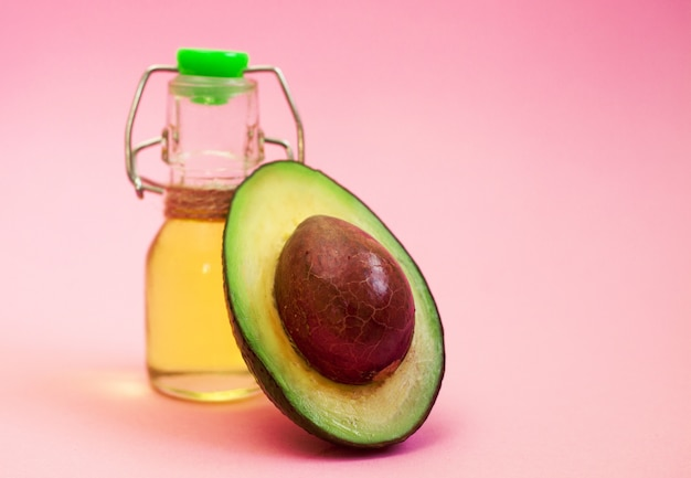 Avocado und avocadoöl in der flasche auf rosa hintergrund.