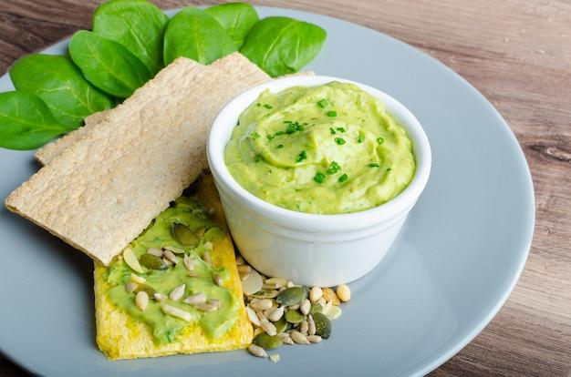 Avocado und guacamole auf holztisch