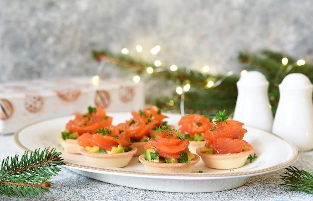 Avocado- und lachsvorspeise auf dem neujahrstisch. törtchen mit fisch.