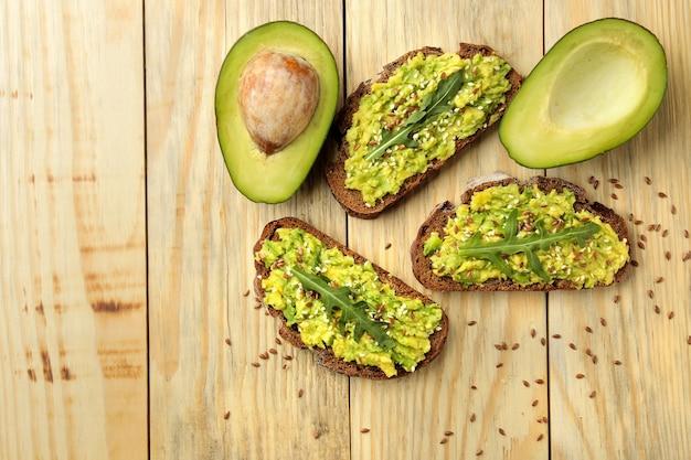 Avocado- und rucola-sandwiches nahaufnahme auf natürlichem holztischansicht von oben