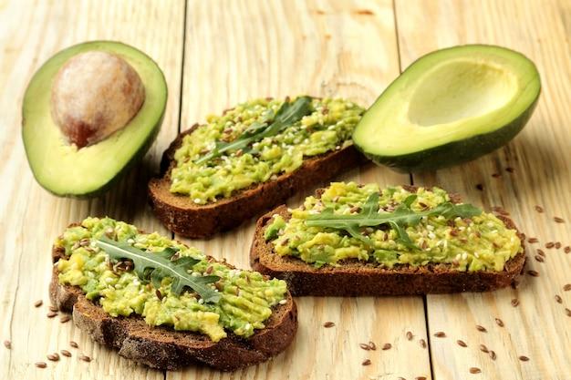 Avocado- und rucola-sandwiches und andere zutaten auf einem natürlichen holztisch.
