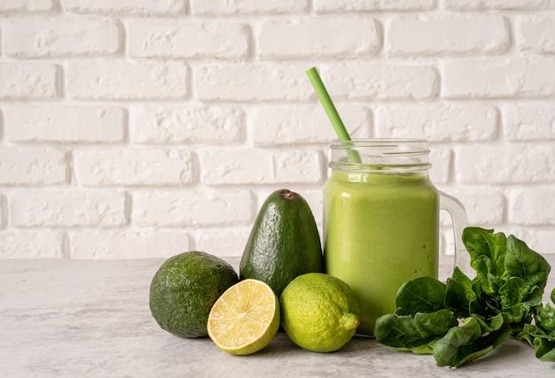 Avocado und spinat smoothie in einmachglas vorderansicht auf weiße backsteinmauer