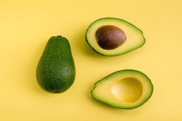Avocadoebene gelegt auf gelben hintergrund