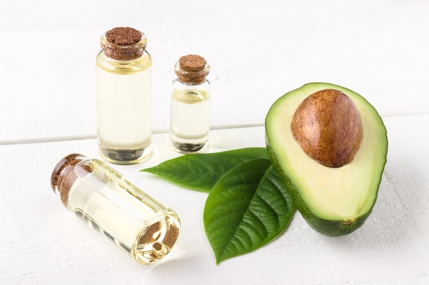 Avocadoöl auf weißem hölzernem hintergrund