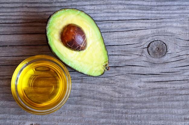 Avocadoöl in einer glasschüssel und in einer neuen hälfte der organischen avocado auf altem holztisch.