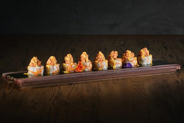 Avocadorolle und frittierte süßkartoffelchips mit nikkei-hühnchen und aji-amarillo-sauce