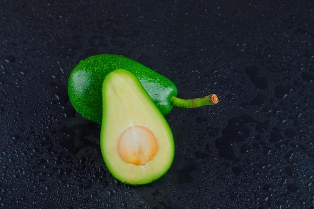 Avocados auf einem dunkelgrauen tisch. draufsicht.