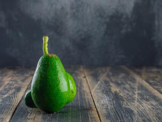 Avocados auf holz- und gipswand. seitenansicht.