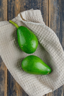 Avocados auf holz- und küchenhandtuchtisch. flach liegen.