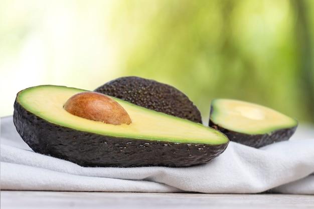 Avocados beinahe eingeschnitten auf weiße serviette und natur