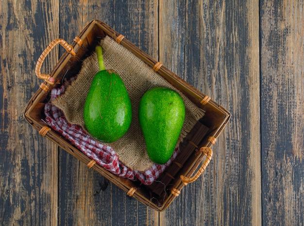 Avocados in einem korb auf einem holztisch. flach liegen.