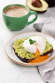 Avocadotoast auf platte mit flüssigem poschiertem ei auf die oberseite und kaffeetasse