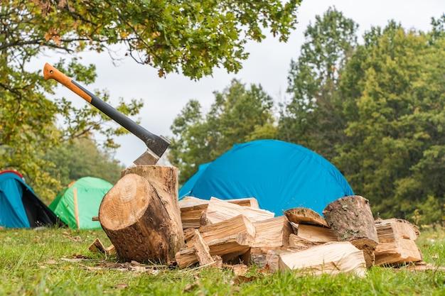 Axt und haufen brennholz für lagerfeuer vorbereitet. zelte im hintergrund. campingkonzept