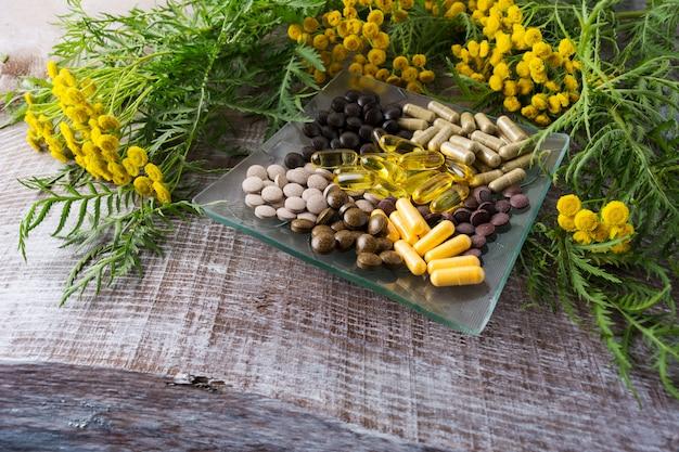 Ayurveda-pillen und gelbes rainfarnkraut