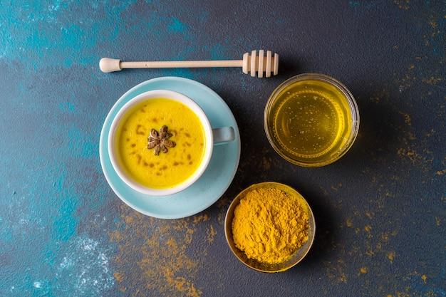Ayurvedic goldene gelbwurz lattemilch gemacht mit gelbwurz und anderen gewürzen auf blauem hintergrund. flach liegen.