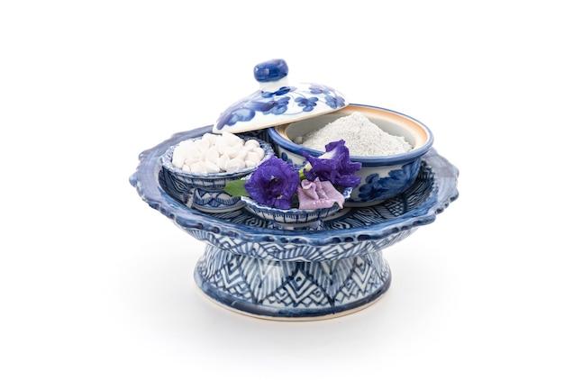 Ayurvedisch parfümiertes pulver mit schmetterlingserbsenblume zum malen auf gesicht und körper für die hautpflege lokalisiert auf weiß.