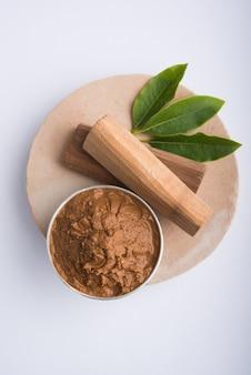 Ayurvedische chandan- oder sandelholzpaste in silberschale mit stäbchensandblättern über sahanor sahana oder rundem steinsockel zur herstellung von paste