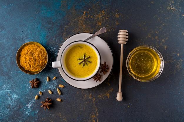 Ayurvedische goldene gelbwurz latte-milch gemacht mit gelbwurz und anderen gewürzen auf blauer oberfläche