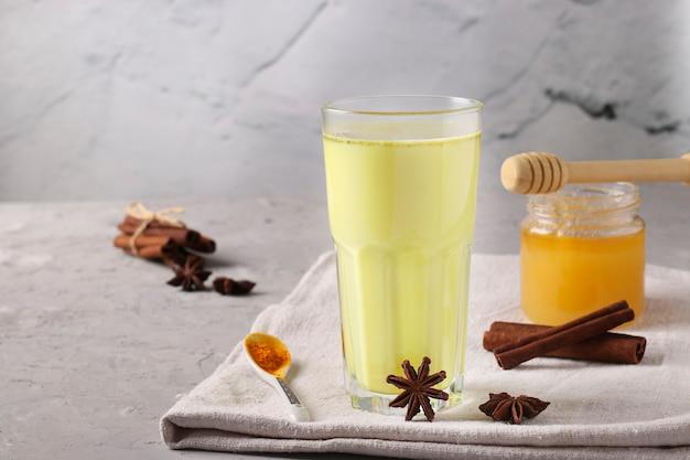 Ayurvedische goldene kurkuma-latte-milch in glas mit kurkumapulver, zimt und anisstern auf grauem tisch, nahaufnahme, kopierraum