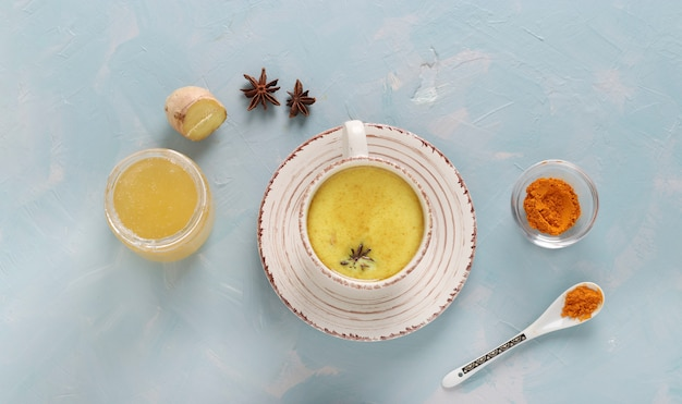 Ayurvedische goldene kurkuma-latte-milch mit kurkumapulver, zimt, ingwer und anisstern in der tasse