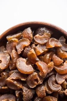 Ayurvedisches amla candy, das getrocknet und salzig-süß oder chatpata im geschmack und verdauung ist. serviert in einer holzschale, selektiver fokus