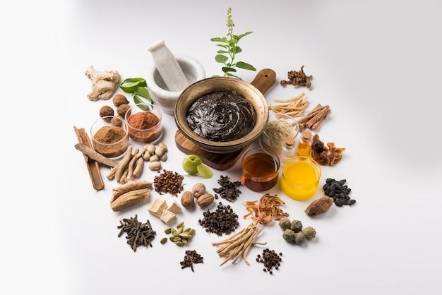 Ayurvedisches chyawanprash ist ein leistungsstarker immunitätsverstärker oder ein natürliches nahrungsergänzungsmittel. serviert in einer antiken schüssel mit zutaten, über stimmungsvollem hintergrund, selektiver fokus