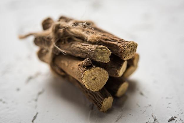 Ayurvedisches mulethi- oder süßholzwurzel-stick oder jeshtamadh-pulver, serviert in einer schüssel auf stimmungsvollem hintergrund