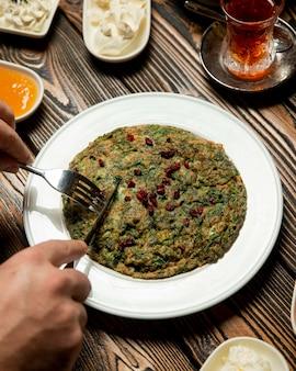 Azeri traditionelles kyukyu mit berberitzenbeere und schale heißem tee