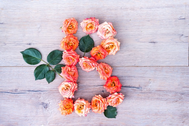 B, rosenblumenalphabet lokalisiert auf grauem hölzernem hintergrund, flache lage