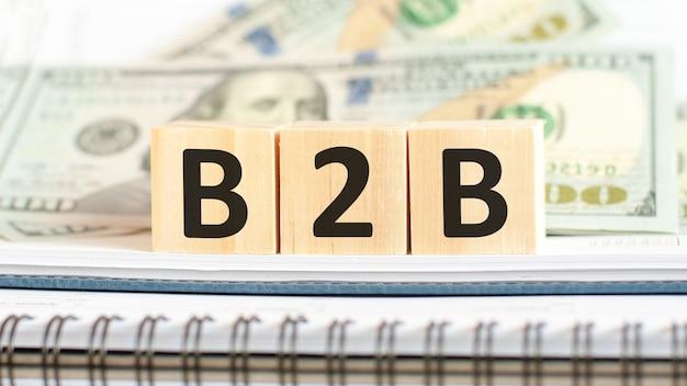 B2b. b2b-abkürzung für business to business. geschäftskonzept auf hölzernen würfeln und dollarhintergrund