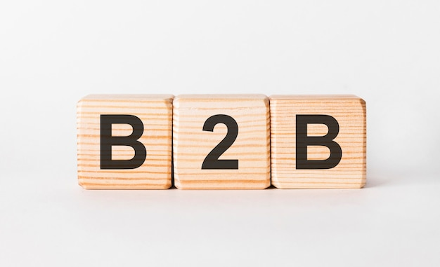 B2b-buchstaben von holzklötzen in säulenform auf weiß