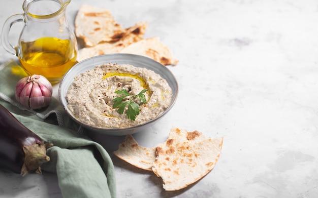 Baba ganoush, ezme der orientalischen, levantinischen küche mit lavash und kräutern aus gebackener aubergine mit sesampaste mit zutaten. platz kopieren
