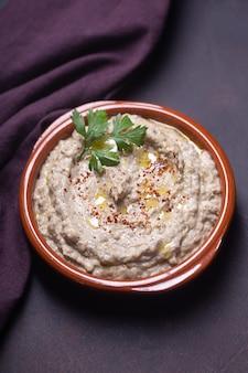 Baba ganoush, ezme eastern levantine cuisine in einem teller mit kräutern gegossen mit olivenöl und kräutern auf dunklem hintergrund