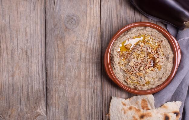 Baba ganoush levantine cuisine aperitif aus gebackener aubergine und sesampaste mit olivenöl, gewürzen, kräutern und walnüssen, lavash auf einem hölzernen hintergrund mit einer serviette. platz kopieren