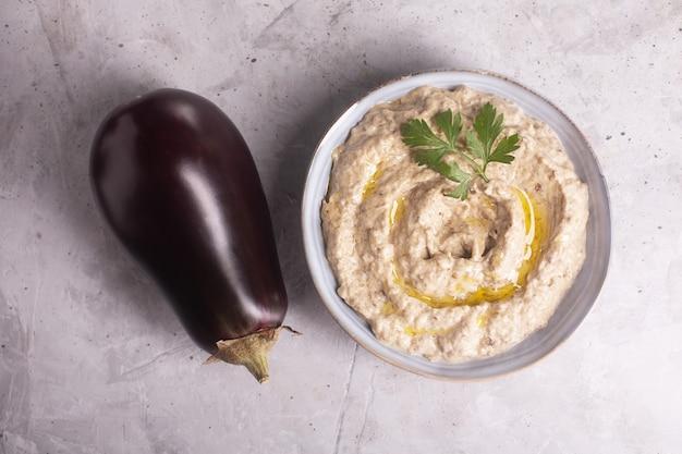 Baba ganoush levantinische küche vorspeise aus gebackenen auberginen und sesampaste mit kräutern und olivenöl auf betonhintergrund