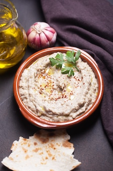 Baba ganoush vorspeise, ezme der orientalischen, levantinischen küche mit kräutern, lavash und knoblauch aus gebackener aubergine mit sesampaste auf dunklem hintergrund