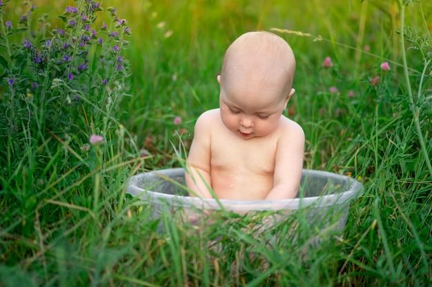 Baby 10 monate alt badet in einem becken im gras im sommer
