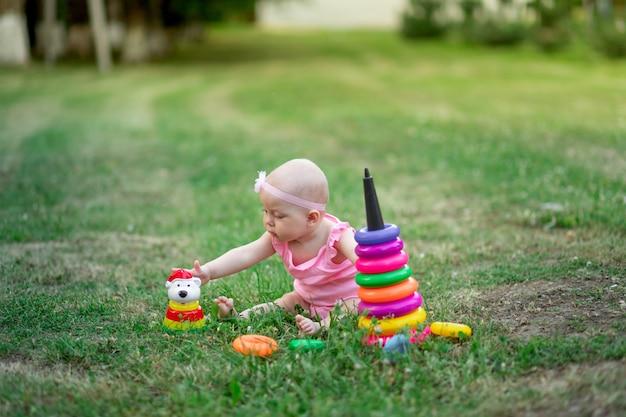 Baby 10 monate alt, das im sommer auf dem gras sitzt und pyramide spielt