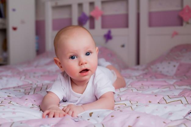 Baby 5 monate in einem weißen body, der mit einer rosa decke auf dem bett liegt