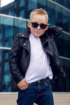 Baby 7 - 8 jahre in sonnenbrille und schwarzer lederjacke lächelnd